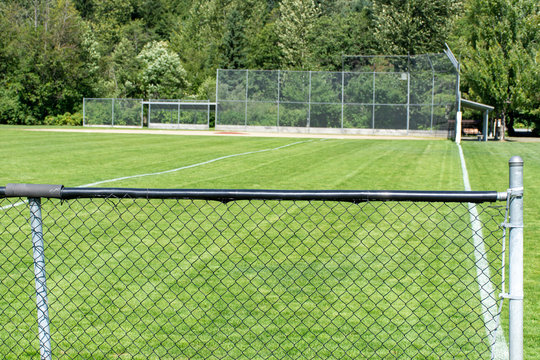 Empty baseball or softball diamond from the back fence and foul line looking towards the grass and trees in Whistler, British Columbia, Canada.