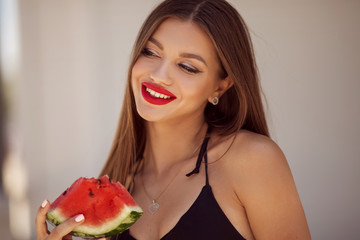 Fashion portrait of a sexy girl with perfect makeup is eating watermelon on the beach