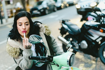 Beautiful brunette woman, middle age, painting her red lips in a mirror of a motorcycle.