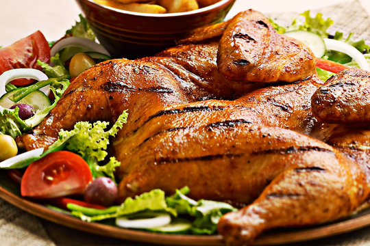 Portugese grilled spatchcock chicken on a bed of salad
