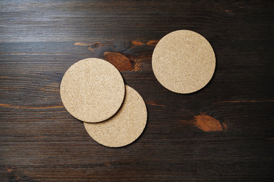 Blank cork beer coasters on wood table background. Flat lay.
