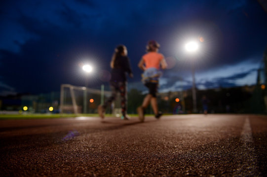 two young sport females running on outdoor stadium track at twilight under bright lights