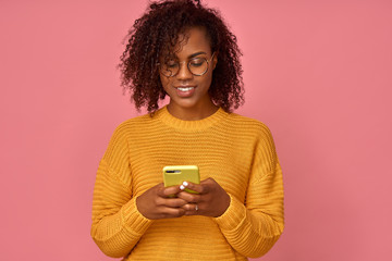 Satisfied lovely black woman holds modern cell phone, texts with friend online in chat, in an orange sweater, poses against pink wall, connected to high speed internet. Shot of teenager with device
