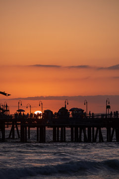 The Santa Monica Pier is silhouetted by the setting summer sun.