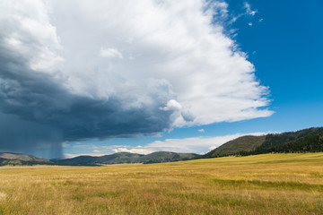 Dramatic storm cloud and rain over the vast landscape and grasslands of the Valles Caldera National Preserve in northern New Mexico