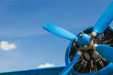 Close up abstract of a vintage airplane propeller engine against blue sky, closeup. Travel concept Wall mural