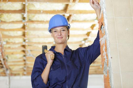 female builder with sledge hammer on her shoulder