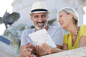 happy senior couple of tourists with map