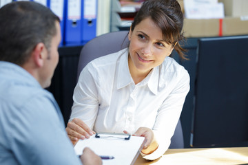 businesswoman showing clipboard to client during meeting