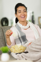 happy woman watching tv with snacks on sofa