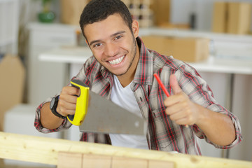 construction worker holding a saw and showing thumbs up approval
