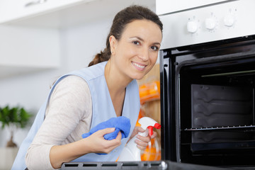 happy woman cleaning oven in kitchen