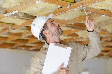 male builder inspecting the ceiling of construction site