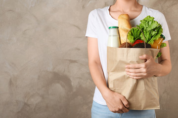 Woman holding shopping paper bag with different groceries against brown background. Space for text