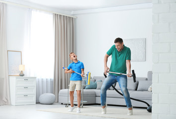 Dad and son having fun while cleaning living room together