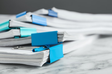 Stack of documents with binder clips on marble table, closeup