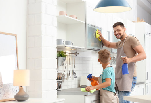 Dad and son cleaning in kitchen together