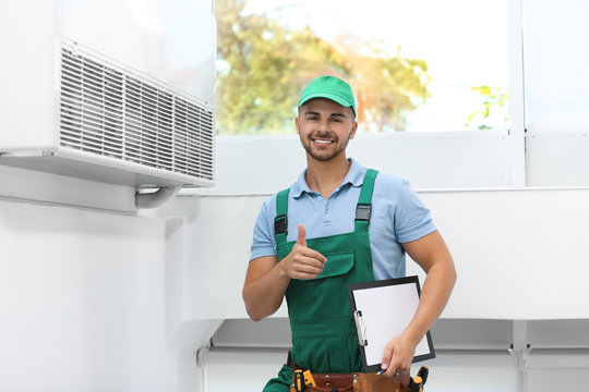 Professional technician with clipboard near modern air conditioner indoors
