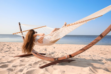 Young woman relaxing in hammock on beach Wall mural