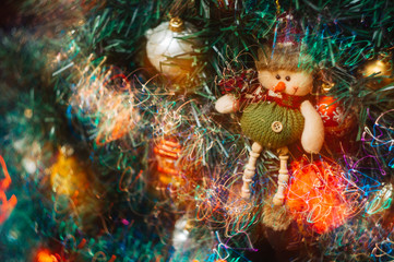 A Christmas toy in the form of a snowman hangs on an artificial Christmas tree with colorful bright lights. Long exposure photo.