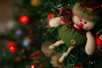 A Christmas toy in the form of a snowman hangs on an artificial Christmas tree with colorful bright lights.