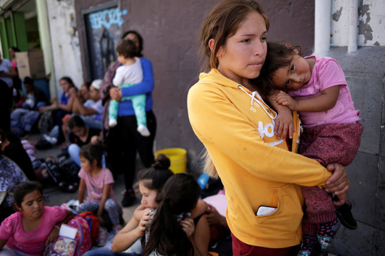 Mexican citizens fleeing violence, queue to cross into the U.S. to apply for asylum at Paso del Norte border crossing bridge in Ciudad Juarez