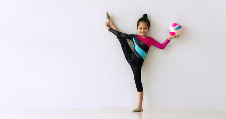 Acrobat little cute girl standing one leg while holding color ball in her hand in the room on white background. Lovely child girl doing gymnastics balance her body on the floor. Exercise concept.