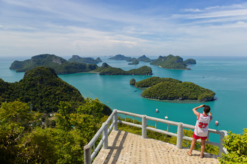 A tourist is taking a photo at viewpoint deck in Koh Wua Ta Lap, blue turquoise ocean and group of islands in Ang Thong National Marine Park in the Gulf of Thailand. Surat Thani, Thailand