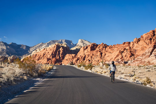african american woman riding bicycle through red rock canyon park