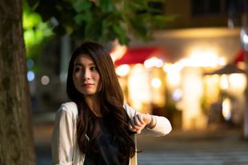 夜の町並みを背景に待ち合わせをする若い女性 Wall mural
