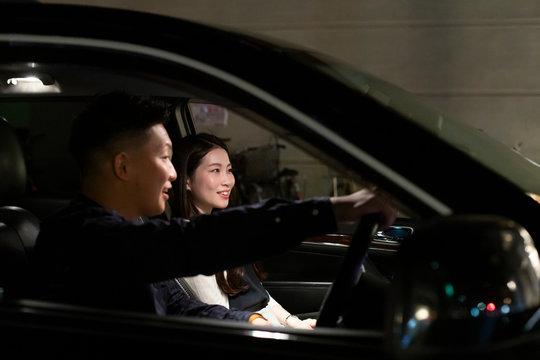 夜の車の中で楽しそうに会話をする若い男女