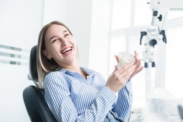 Portrait of a happy attractive girl in a dental chair. Laughing girl at the dentist's appointment with a jaw model in her hands