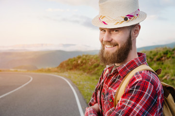 Portrait of a bearded happy smiling traveler hipster with a backpack in a plaid shirt and a hat next to an unknown car stands on the road at sunset in the mountains. Happy and confident travel concept