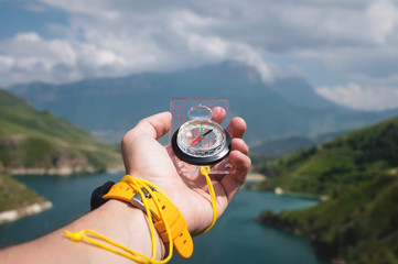 Close-up wide angle male hand with a yellow watch bracelet holds a magnetic navigation compass against the backdrop of a beautiful landscape in the mountains with a mountain lake.