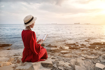 An attractive Caucasian girl in a red bright dress and a straw hat sits on a large stone by the sea at sunset and reads an interesting book on the sea horizon. Back view