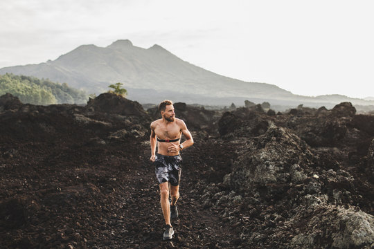 Young athletic man with beard trail running fast outdoors. Topless body and chest heart rate monitor. Mountain view on background.