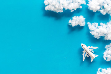 Fly by plane concept. Airplane model and clouds on blue background top view frame space for text