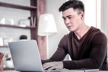 Young handsome man working with his laptop from home