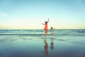 Happy mother and young daughter on the beach.