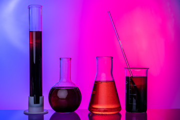 Laboratory glass tubes with chemicals on bright pink background