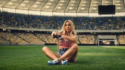 Girl with a joystick on the football field. Beautiful blonde with big breasts. The girl is playing. Large screen on the background.