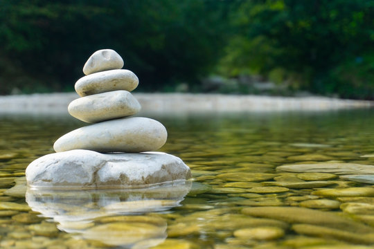 Harmony, balance and simplicity concept. A stone pyramid on the background of river water. Simple poise pebbles, rock zen sculpture