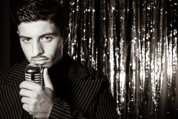 Handsome latino man singing in front of vintage microphone in nightclub with silver curtain in background