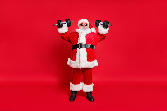 Full length body size view of his he nice attractive cheerful cheery glad strong bearded Santa working out barbell isolated over bright vivid shine red background