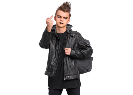 Angry teen boy student with backpack in style of punk goth dressed in black showing middle finger, isolated on white background. Teenager Back to school. Child with spooking make-up shows bad sign.