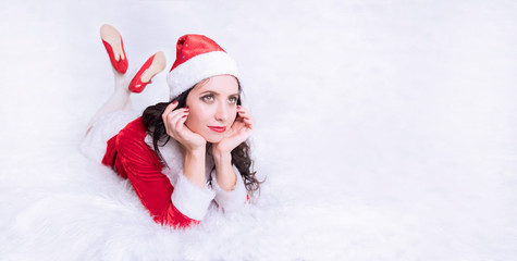beautiful girl in Santa's hat, closeup portrait. Girl lying resting on the couch and look up. Carnival costume for the new year. space for text and design