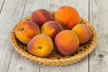 Peach heap in the wooden basket