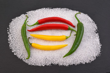 Mix of chili peppers with salt and rosemary on black stone. Black food background with spices.