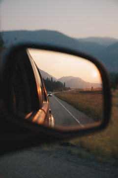A rearview mirror reflecting a landscape with mountains, a sunset and a road.