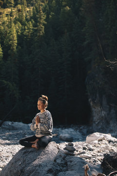 young woman in a knitted sweater are meditating on a rock in a dark valley in Canada.